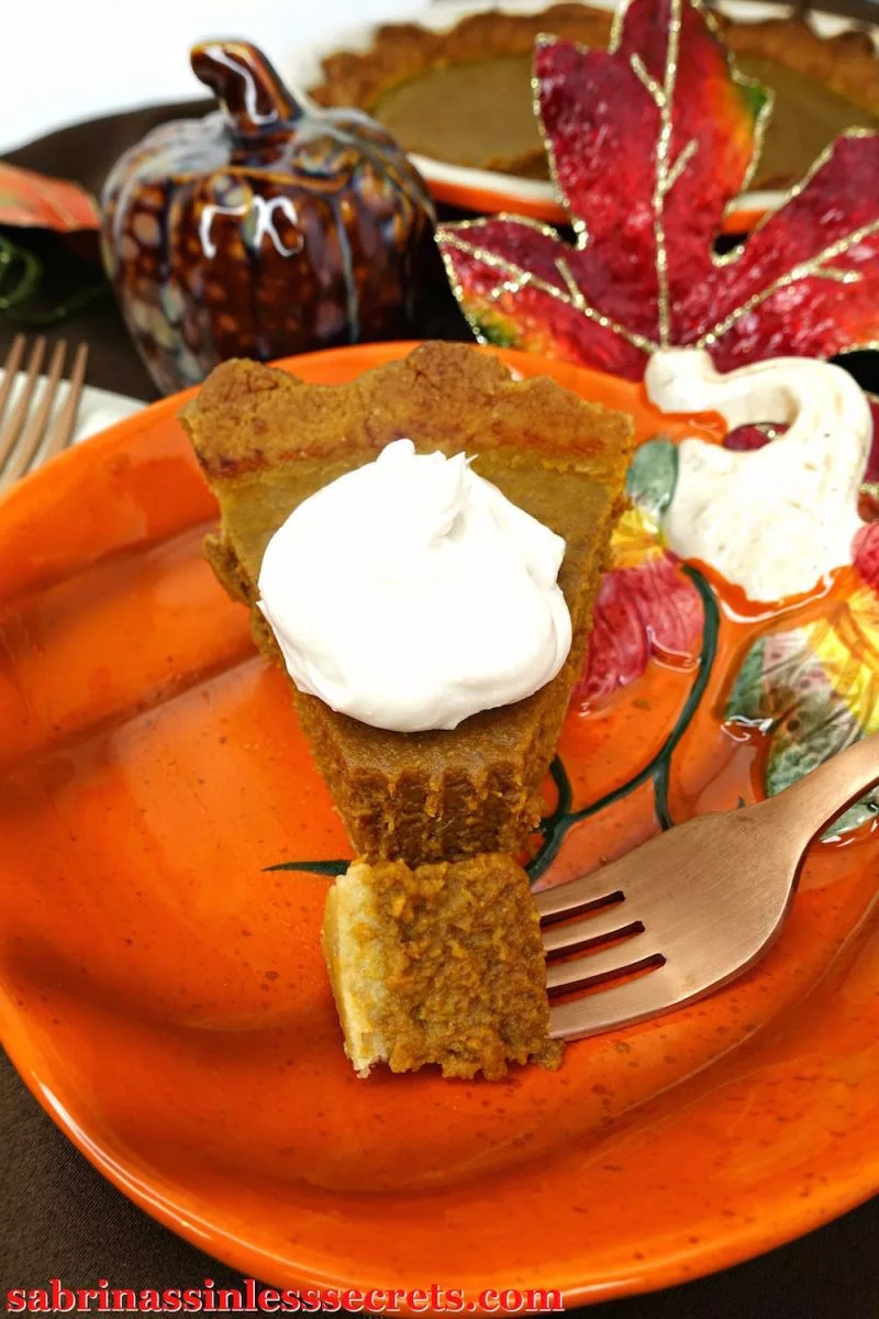 Closeup of a slice of pumpkin pie with a piece on a fork