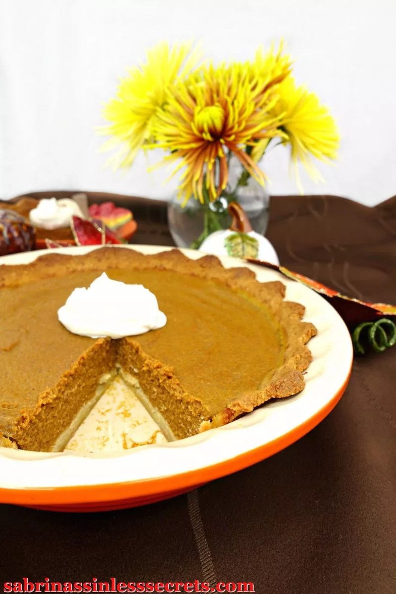 Pumpkin pie in a dish with one slice removed, topped with whipped cream.