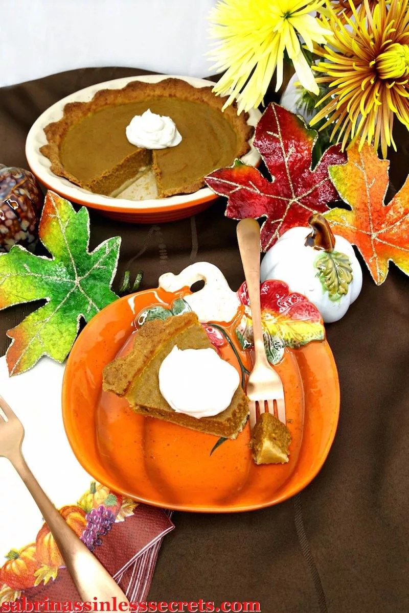 Pumpkin pie set out on a table with fall decorative spread.