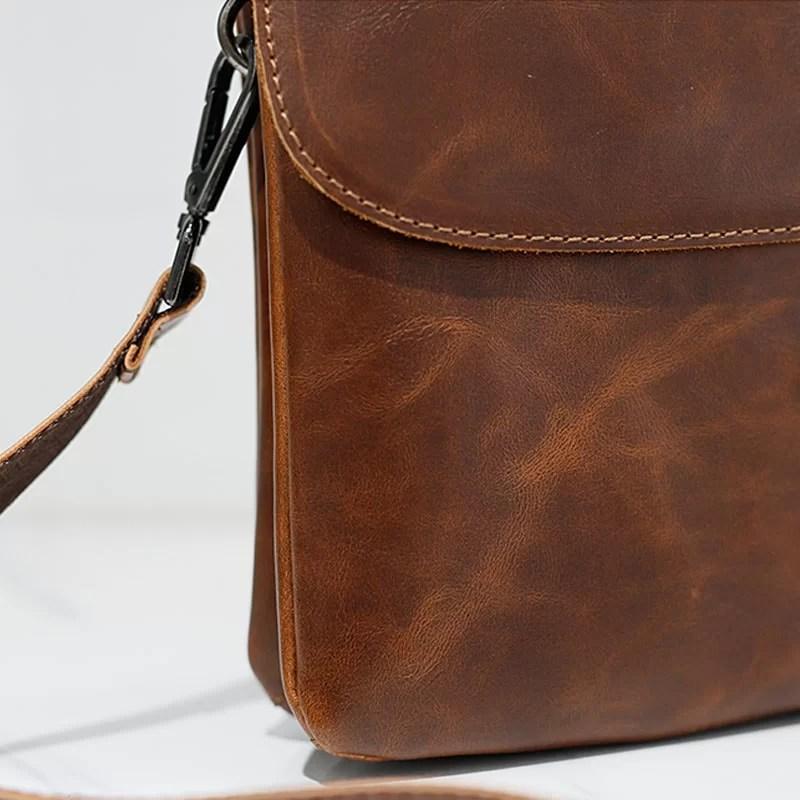 Détails du petit sac besace reporter pour homme en cuir marron.
