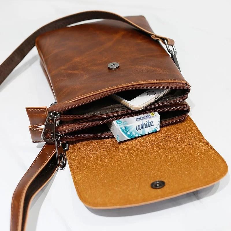 Intérieur du sac besace reporter pour homme en cuir marron avec sa bandoulière.