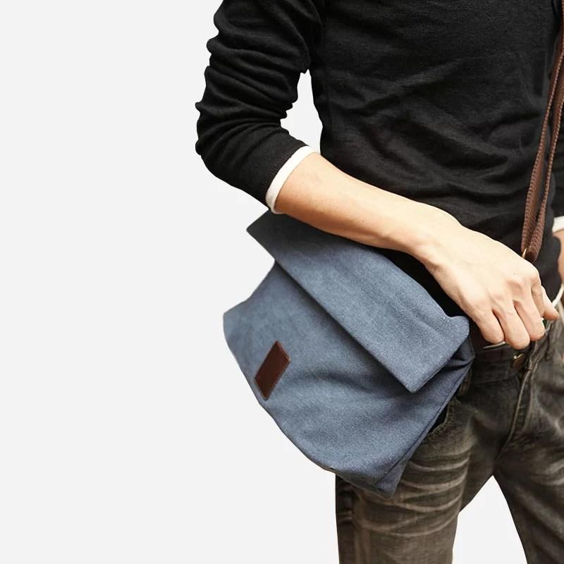 Sacoche pour homme en toile bleu avec sa bandoulière brune porté par un modèle.