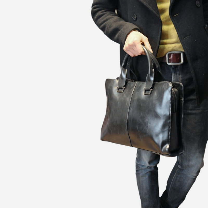 Sac porte-documents et ordinateur pour homme en cuir noir porté main.
