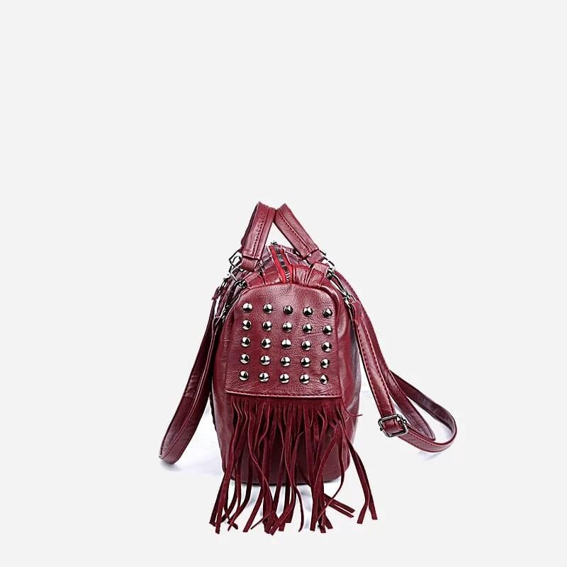Côté du sac à main bandoulière en cuir rouge clouté et frangé.