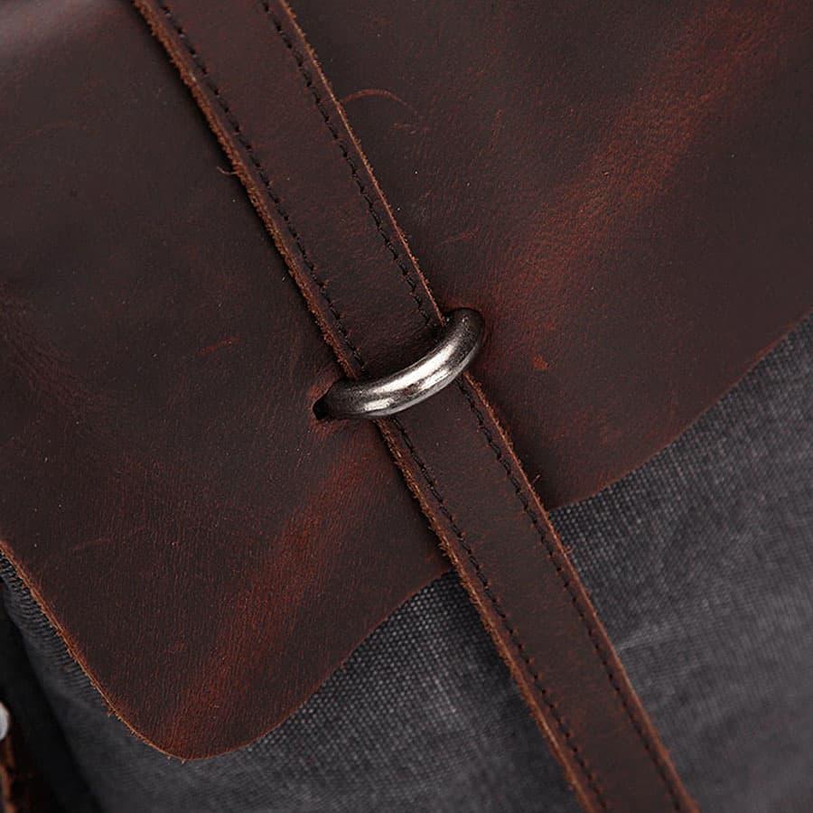 Rabat en cuir véritable avec bride et encoche à rivet métallique.