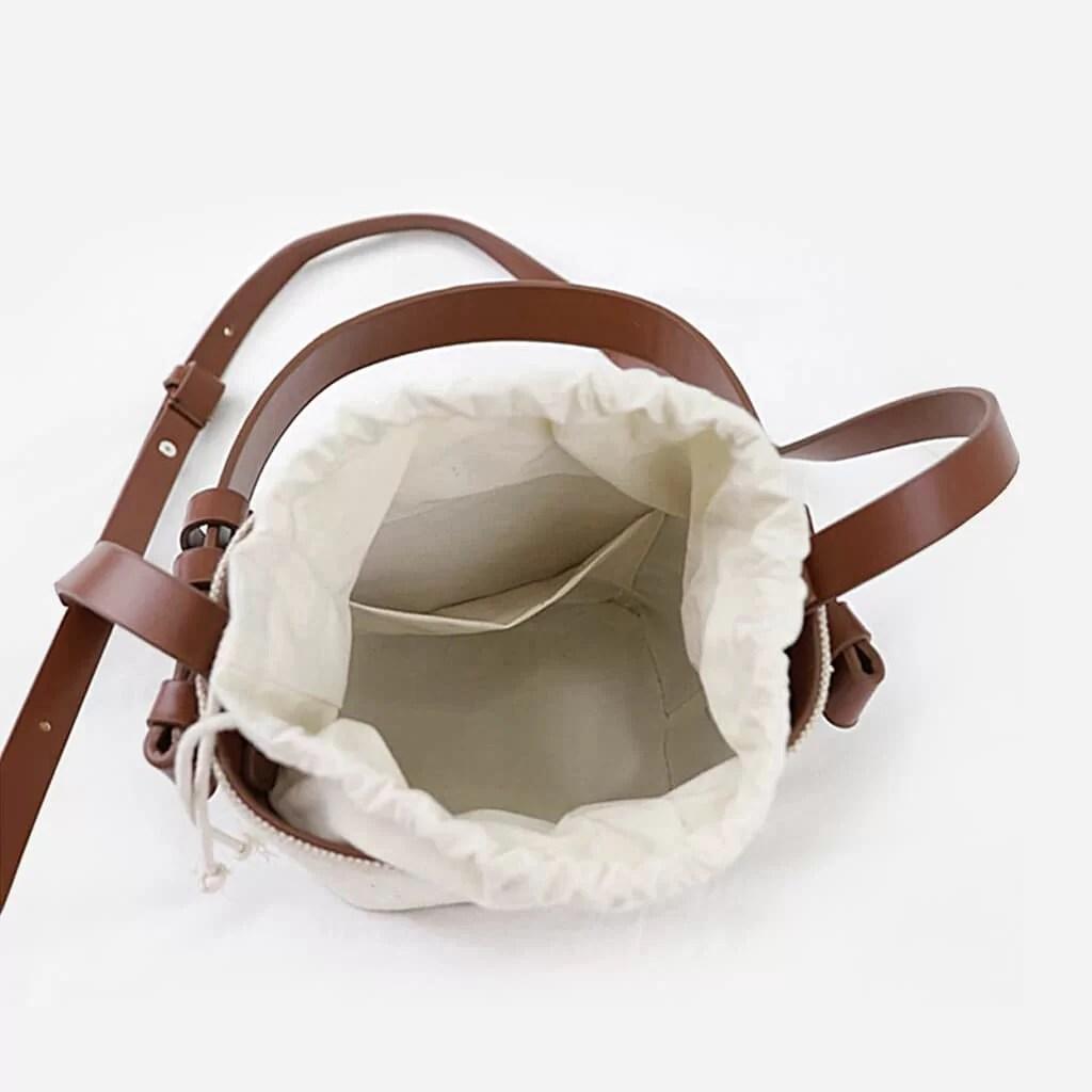 Intérieur du sac seau à bandoulière en toile blanc cassé/beige et cuir marron.