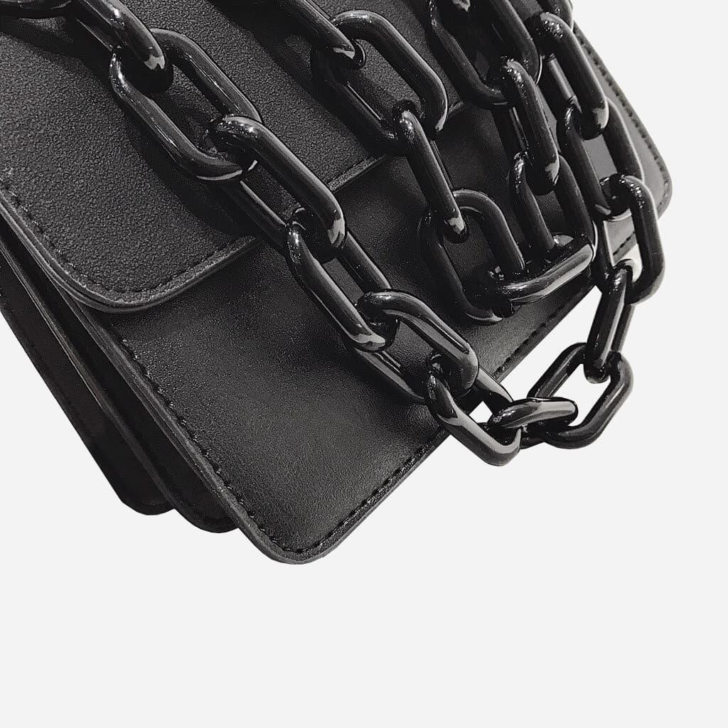 Détail de la bandoulière à grosse chaîne noire en métal du sac besace.