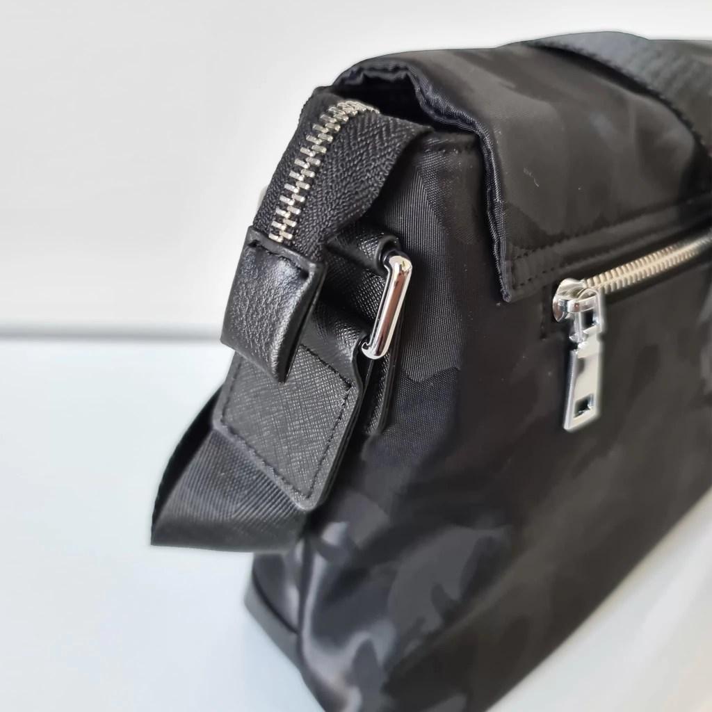 Zoom fermeture éclair et encoche en cuir safiano noir.
