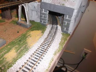 Ballast on the track as it heads into the tunnel.