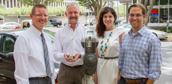 """Matt Eierman, Mike King, Linda tucker, and Carlos Eliason photographed with award next to a """"smart"""" meter in downtown."""