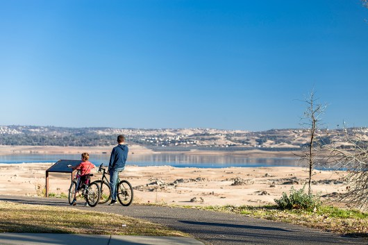 Spectators admire a shoreline that was once covered with water. The historically low shortage of water in the Folsom Reservoir is striking, enough so that these cyclist take a break to consider the scarcity of this precious resource.