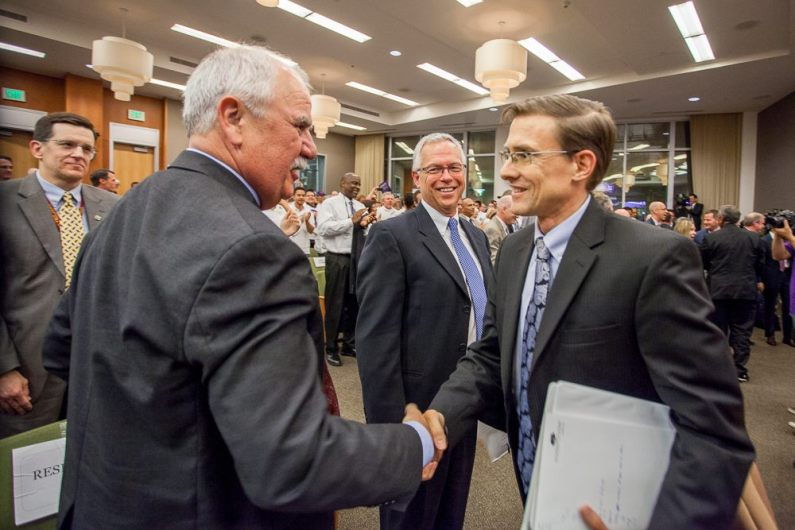 Russ Fehr, City Treasurer and Desmond Parrington shake hands after a momentus Council meeting that approves the development of the Entertainment & Sports Center project. Assistant City Manager, John Dangberg in background.