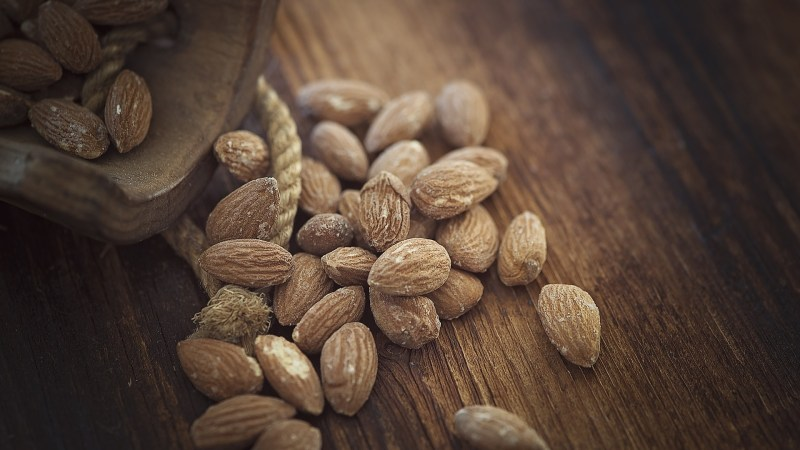 Almonds displayed on a wooden surface.