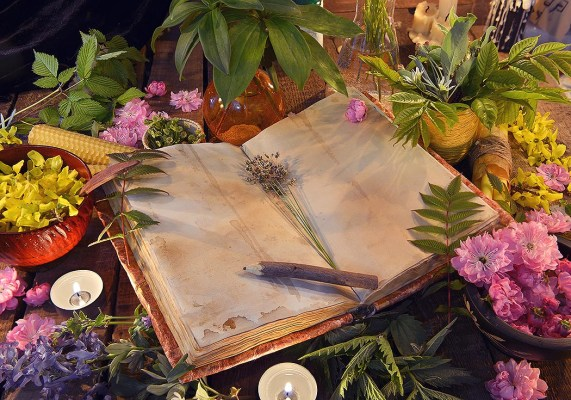 Witch's herbal book with candles and flowers.