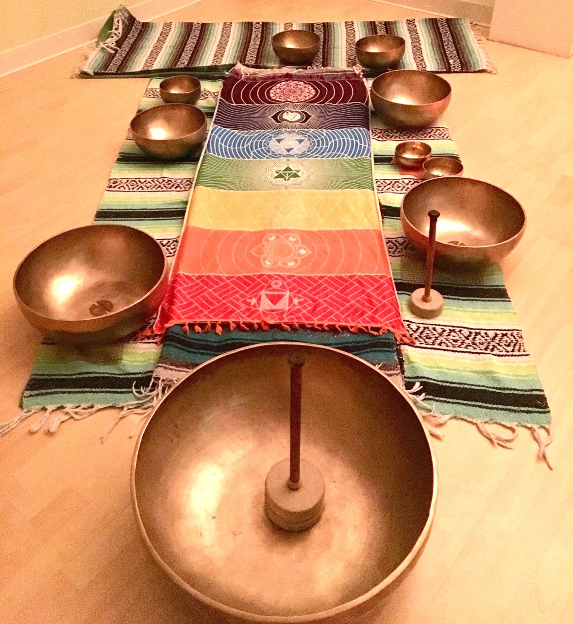 Healing bowls on yoga blankets with a colorful chakra blanket on top.