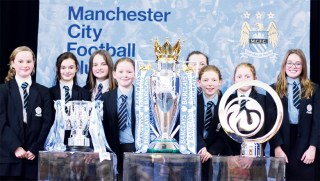 GIRLS: These footie mad youngsters wanted their photos taken with the trophies