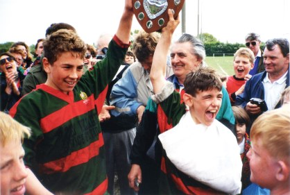 A winner in schoolboy rugby, Kevin (left) lifts a trophy at an early age