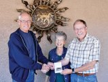 Chuck and Shirley Kaltenbach won the recent SaddleBrooke Hiking Club Geocache Competition and were presented with a Summit Hut gift certificate by GPS Workshop organizer Roy Carter; photo by Karen Carter.