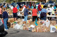 Volunteers sort food for the annual community food drive benefiting the Tri Communities.