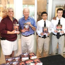 SaddleBrooke Rotarian George Corrigan (center) distributing books to students and staff at Sycamore Canyon Academy