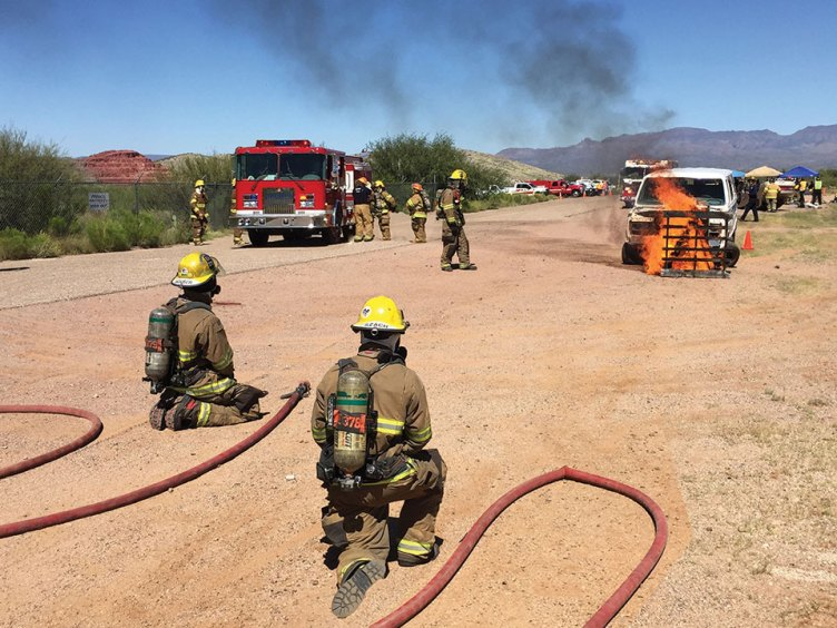 The fire fighters at a training session where they are learning the proper procedures to extinguish a vehicle blaze; Photo by Steve Weiss