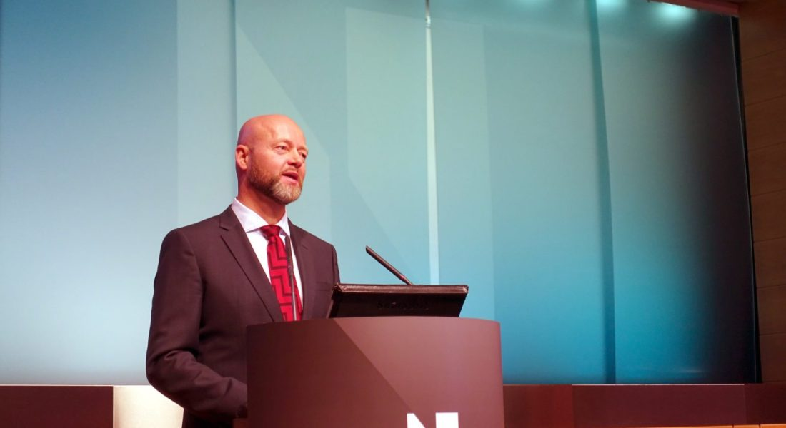 A person with a short beard and shaved head wearing a black suit jacket with a red tie stands behind a podium and appears to be in the middle of a speech.