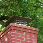 Aluminum chimney cap on top of brick chimney