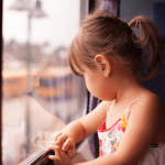 Child looking out home window