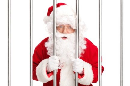 Sana Claus standing behind bars in jail