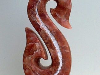 Red stone abstract sculpture on white stone base