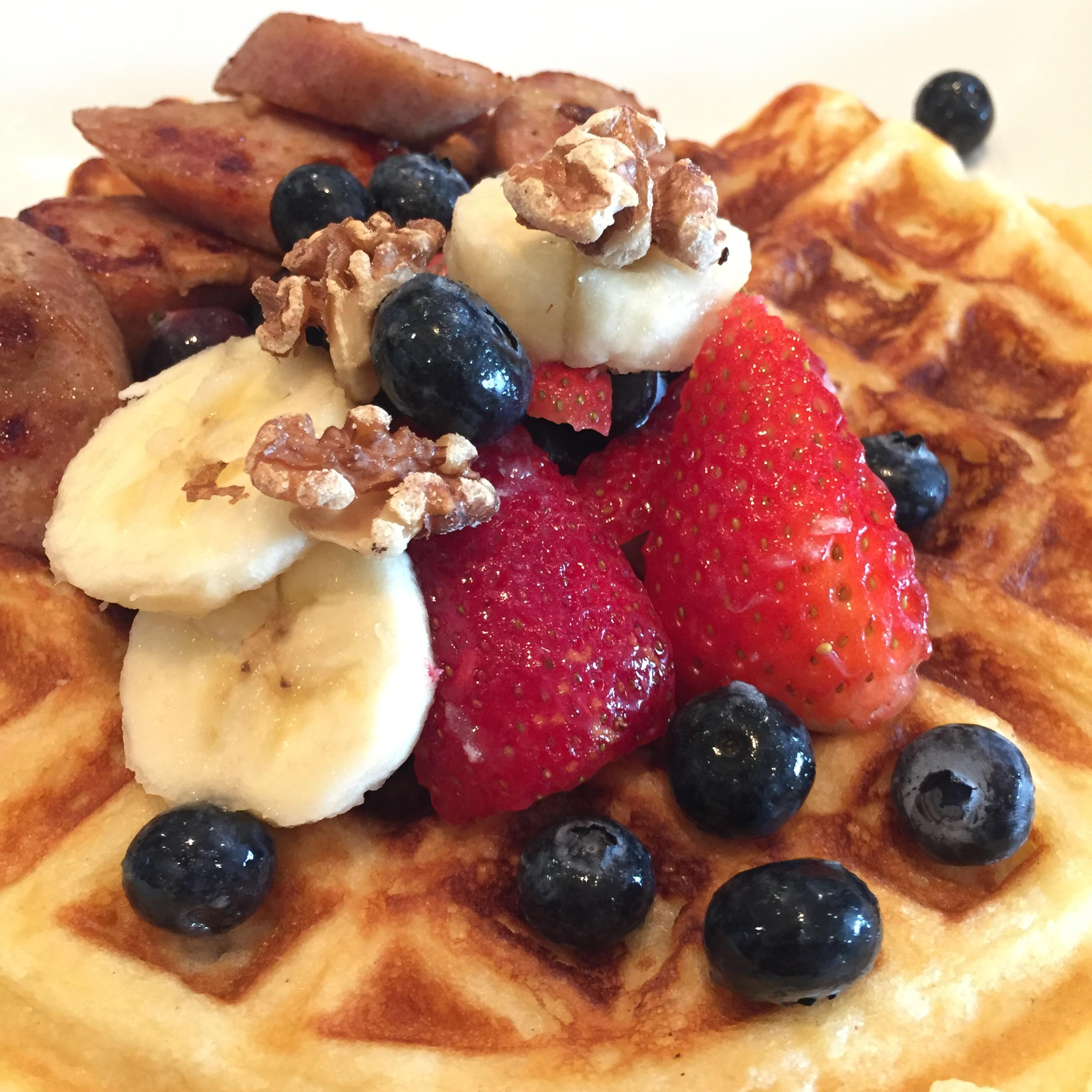Buttermilk waffles, topped with berries and walnuts, with a side of chicken-apple sausage