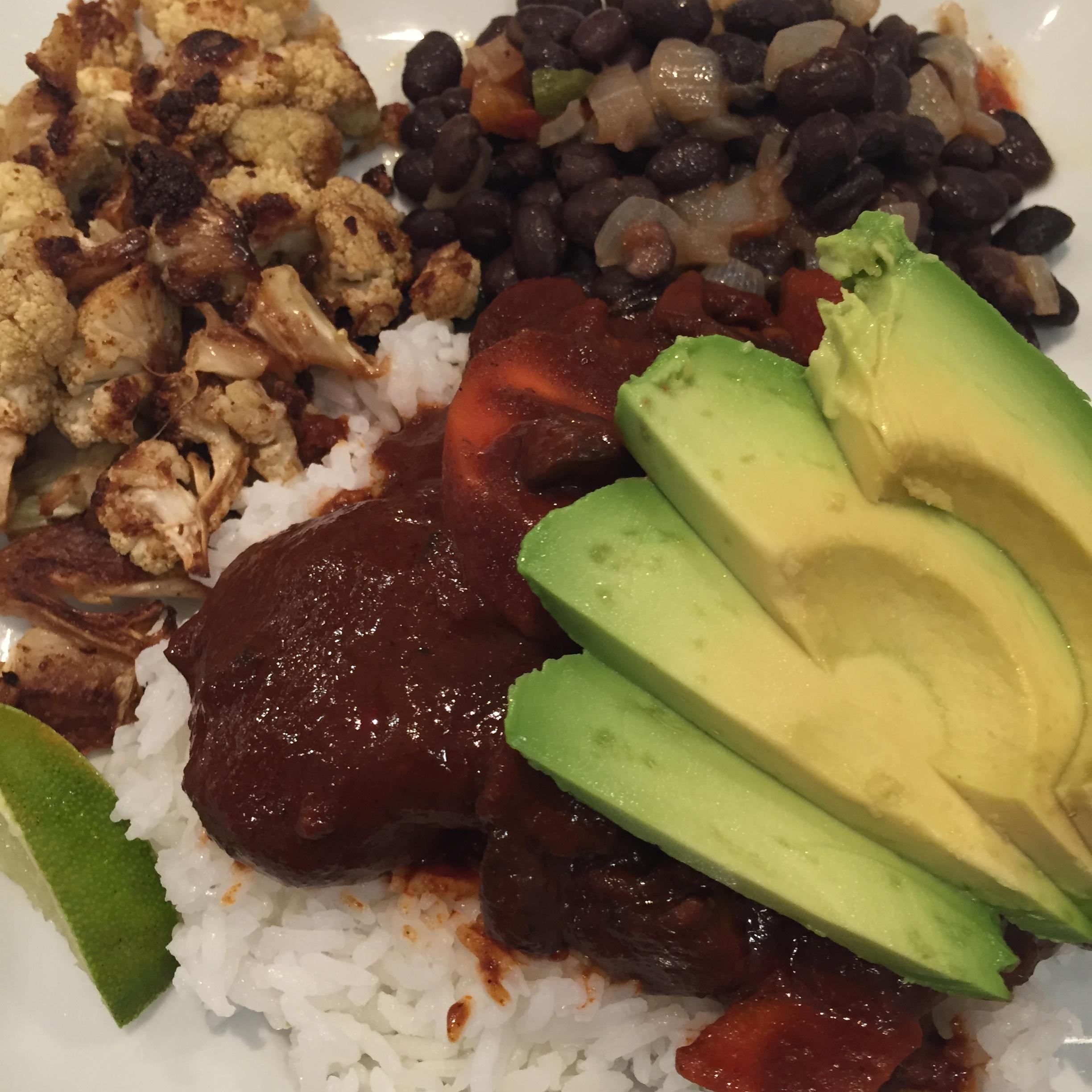 Chicken mole with sliced avocado. Sides of roasted cauliflower and black beans.