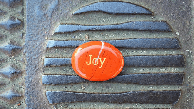 Red stone with the word Joy on cast iron