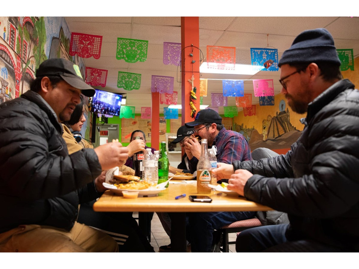 Rodrigo Cala (left) and Aaron Blythe (right) eat a late lunch with Javier Garcia (center) and his family after meeting about their cooperatively owned and run farm, Agua Gorda at Mi Pueblito, Jose Garcia's market and restaurant in Long Prairie, Minn. on February 27, 2021.
