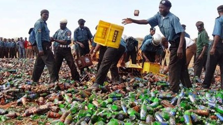 Some Hisbah men destroying seized alcoholic products from Sabon Gari