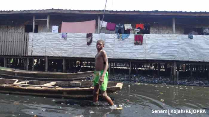 Young boy makes his way through the now shallow water in Makoko.