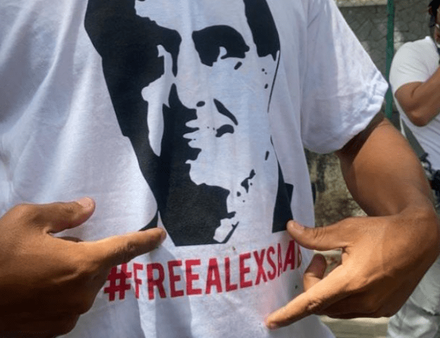 """File Photo: A protester putting on """"Free Alex Saab"""" shirt"""