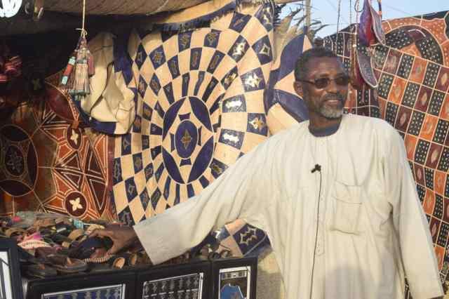 Baba Ousmane, fidèle du festival, devant sa Maroquinerie