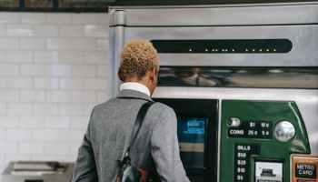 anonymous black woman standing near metro ticket machine