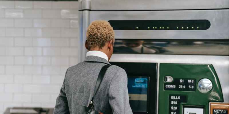 anonymous black woman standing near metro ticket machine