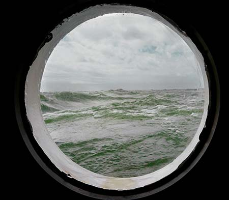 Rough ocean waves seen through the porthole of a voyaging boat. Pictured for an article about using oil on storm waters as a storm tactic.