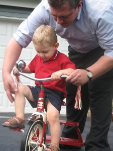 Dad helping his son ride a tricycle
