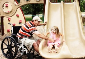 Father helping his daughter on a slide