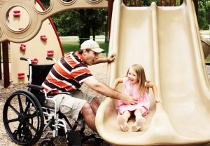 Dad in wheelchair helping daughter on a slide