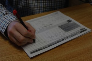 Close up of hand filling out paperwork