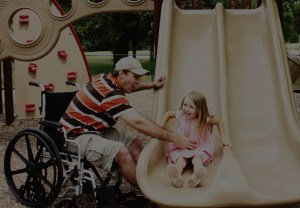 Father in a wheelchair assisting his daughter on a slide at a playground
