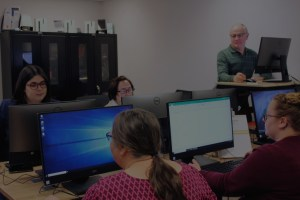 A group of people sitting at computers in a technology lab