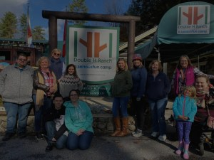 SAIL employees gathering around the Double H Ranch sign during an event
