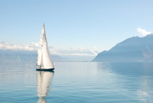 sailboat on a lake surrounded by mountains