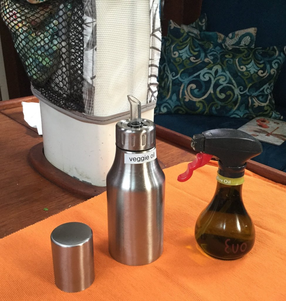 A stainless carafe with tight cap for pouring oil and a small bottle for spraying oil.